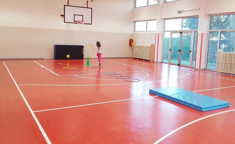 Young girl is doing exercise in a elementary school gym indoor royalty free stock images