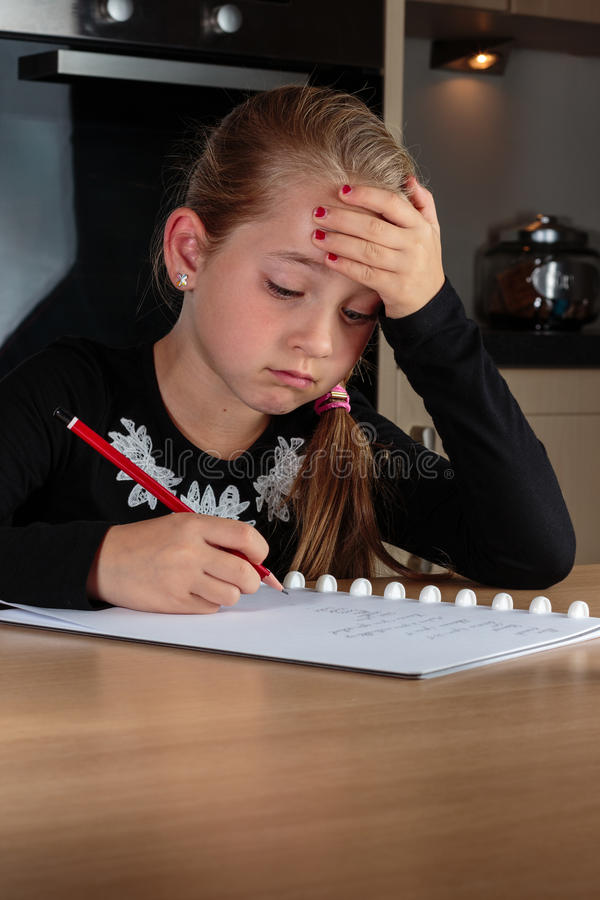 Young girl doing homework at the kitchen table stock photo