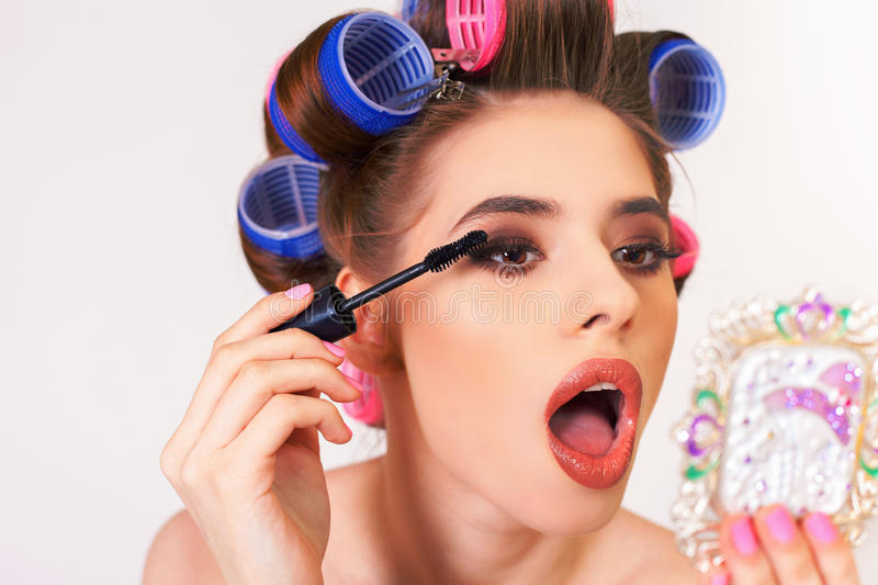 Young girl doing makeup and hairstyle using curlers royalty free stock photography