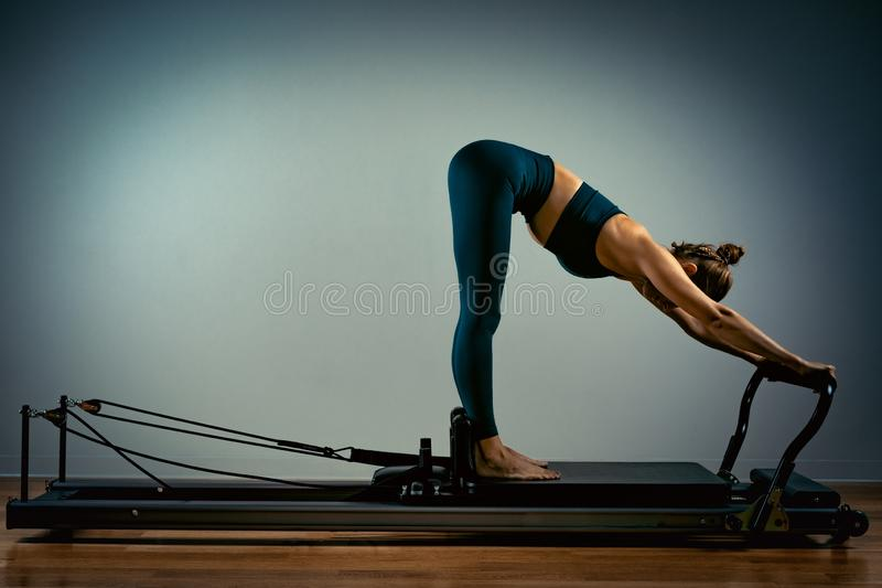 Young girl doing pilates exercises with a reformer bed. Beautiful slim fitness trainer on reformer gray background, low royalty free stock images