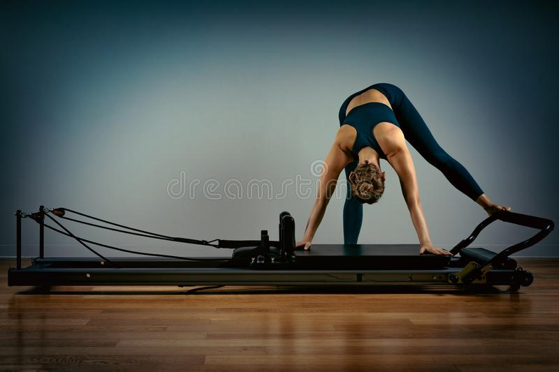 Young girl doing pilates exercises with a reformer bed. Beautiful slim fitness trainer on reformer gray background, low royalty free stock photos