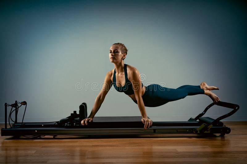 Young girl doing pilates exercises with a reformer bed. Beautiful slim fitness trainer on reformer gray background, low royalty free stock image