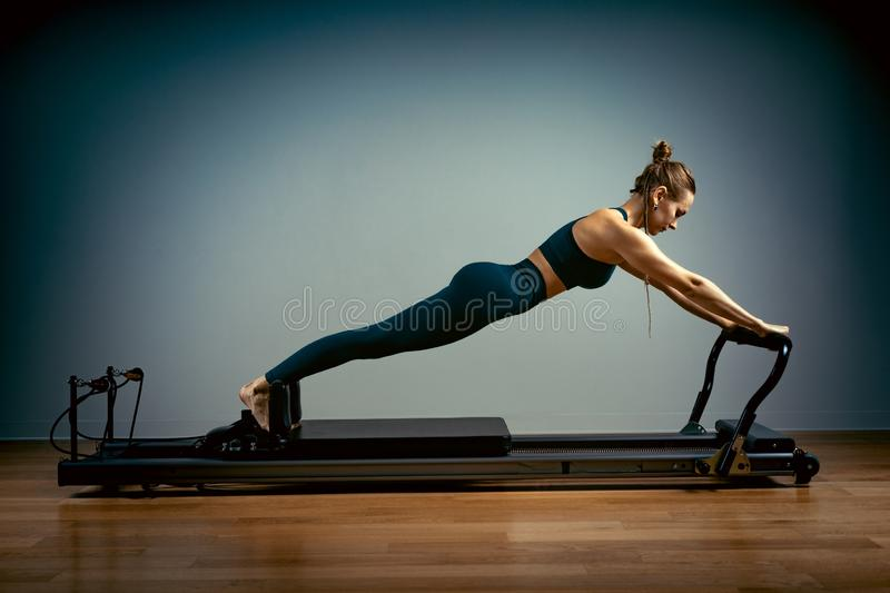 Young girl doing pilates exercises with a reformer bed. Beautiful slim fitness trainer on reformer gray background, low stock photos
