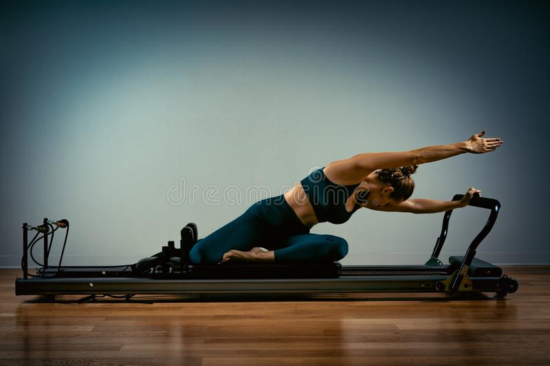 Young girl doing pilates exercises with a reformer bed. Beautiful slim fitness trainer on reformer gray background, low stock images