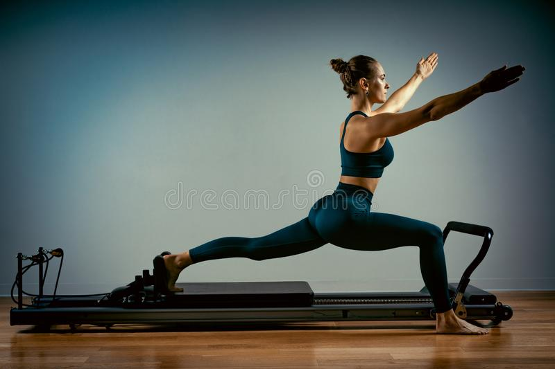 Young girl doing pilates exercises with a reformer bed. Beautiful slim fitness trainer on reformer gray background, low royalty free stock photo