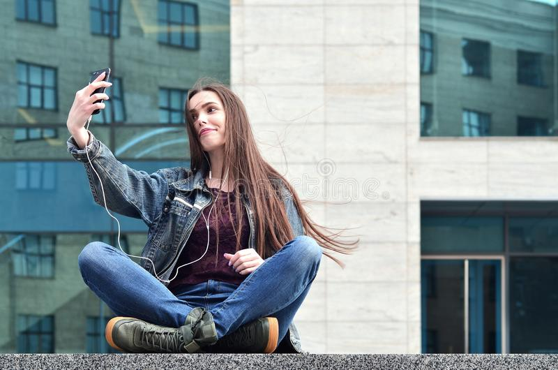 Young girl doing selfie on the background of an office building. Young brunette girl in jeans doing selfie on a smartphone on the background of an office royalty free stock photos