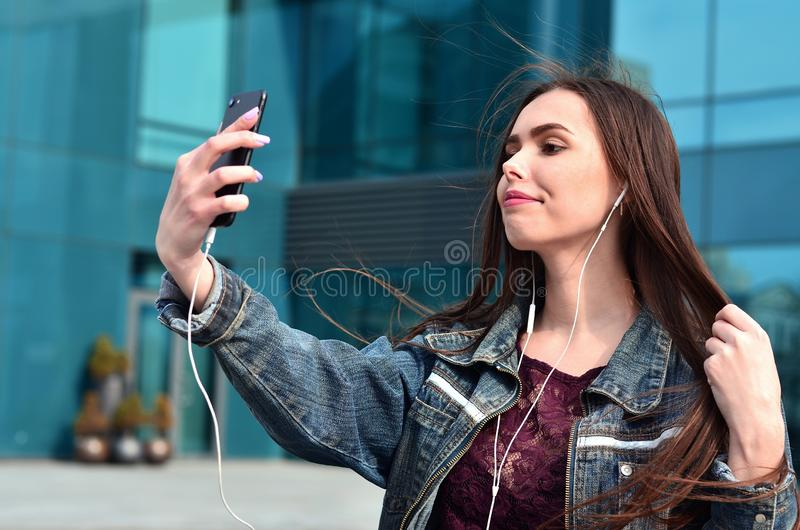 Young girl doing selfie on the background of an office building. Young brunette girl in jeans doing selfie on a smartphone on the background of an office stock photo