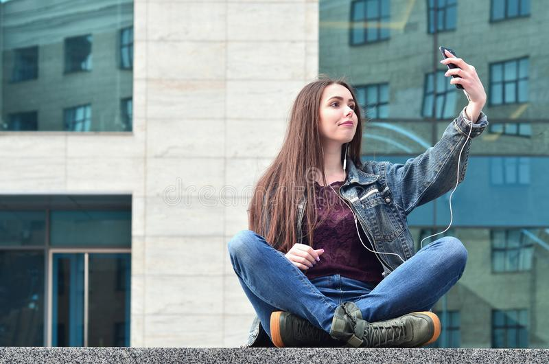 Young girl doing selfie on the background of an office building. Young brunette girl in jeans doing selfie on a smartphone on the background of an office royalty free stock image