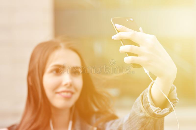 Young girl doing selfie on the background of an office building. Young brunette girl in jeans doing selfie on a smartphone on the background of an office stock images