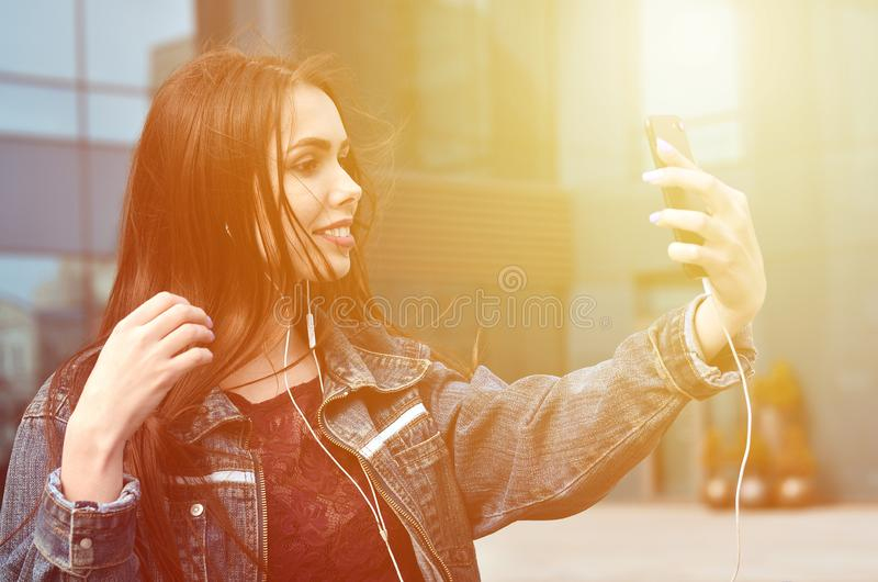 Young girl doing selfie on the background of an office building. Young brunette girl in jeans doing selfie on a smartphone on the background of an office royalty free stock photography