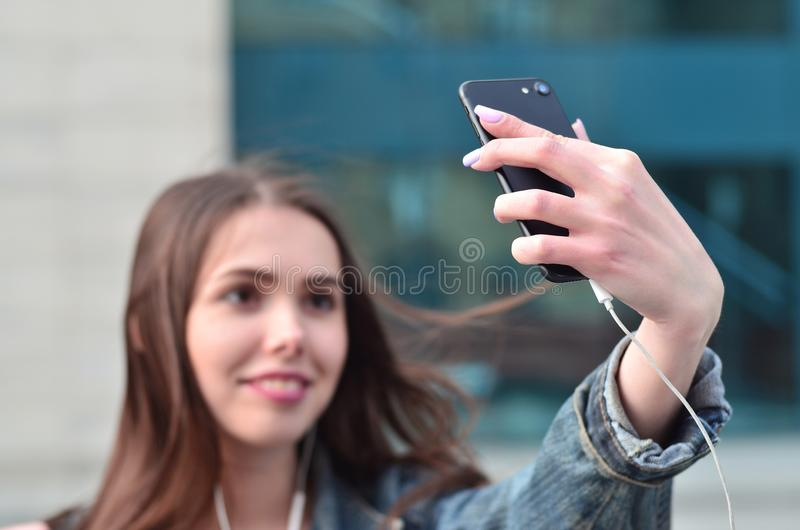 Young girl doing selfie on the background of an office building. Young brunette girl in jeans doing selfie on a smartphone on the background of an office stock image