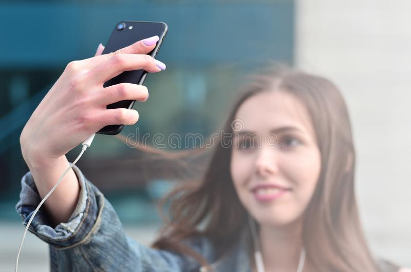 Young girl doing selfie on the background of an office building. Young brunette girl in jeans doing selfie on a smartphone on the background of an office stock photography