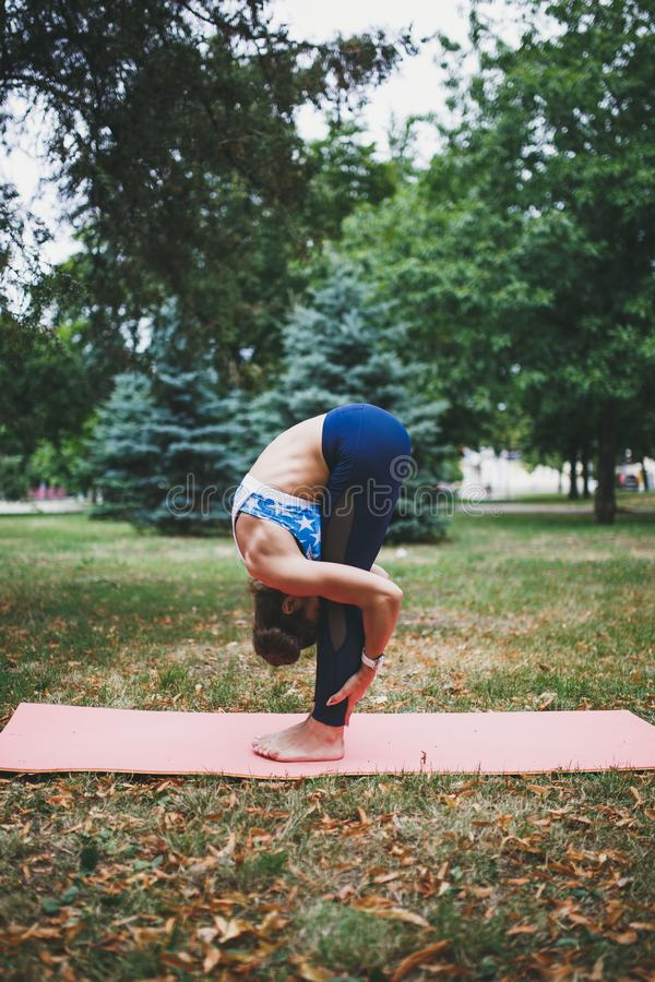 Young girl doing yoga exercise outdoors. stock photography