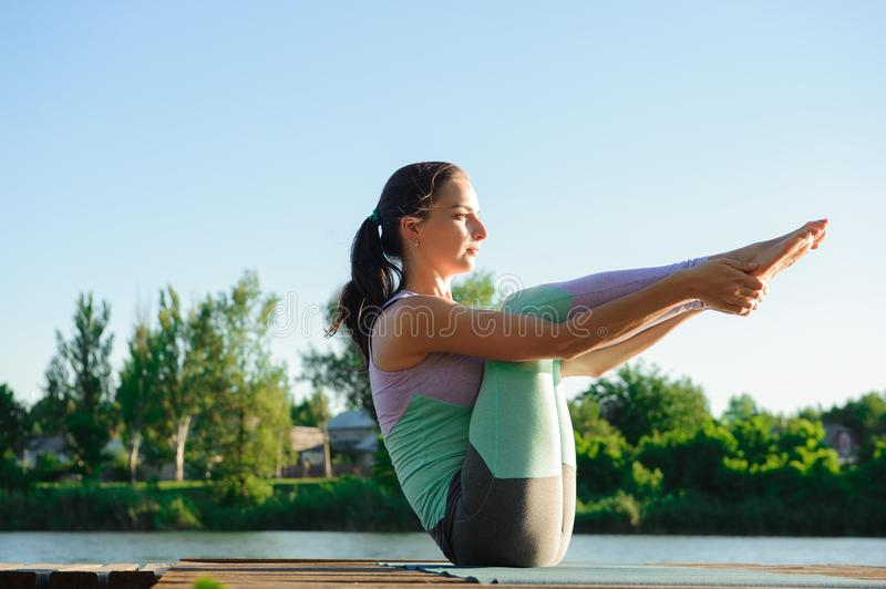 Young girl doing yoga fitness exercise outdoor in beautiful landscape. Morning sunrise. Meditation and Relax royalty free stock images
