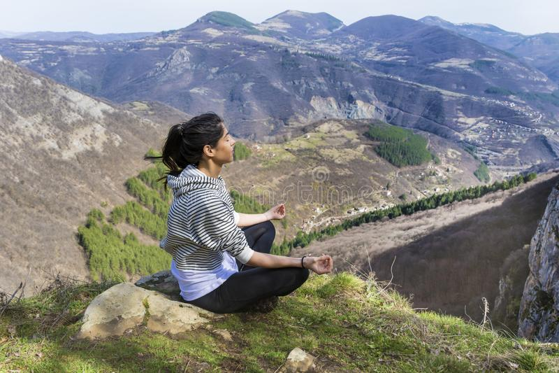 Yoga Woman Meditating in the Mountain. Young girl doing yoga fitness exercise outdoor on a beautiful mountains landscape royalty free stock image
