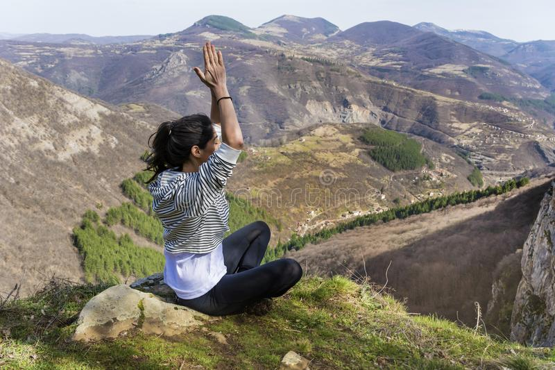 Young Woman Meditating in the Mountain. Young girl doing yoga fitness exercise outdoor on a beautiful mountains landscape stock photography