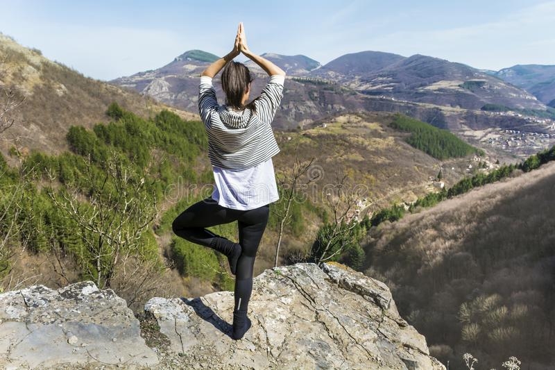Young Woman Meditating in the Mountain. Young girl doing yoga fitness exercise outdoor on a beautiful mountains landscape stock images