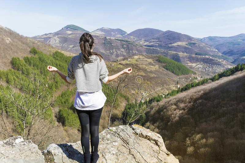 Young Woman Meditating in the Mountain. Young girl doing yoga fitness exercise outdoor on a beautiful mountains landscape royalty free stock photography