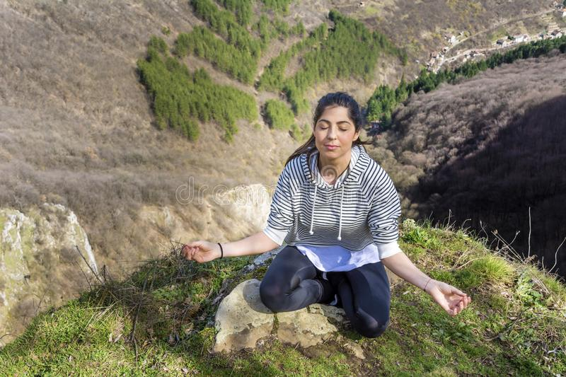 Young Woman Meditating in the Mountain. Young girl doing yoga fitness exercise outdoor on a beautiful mountains landscape royalty free stock photo