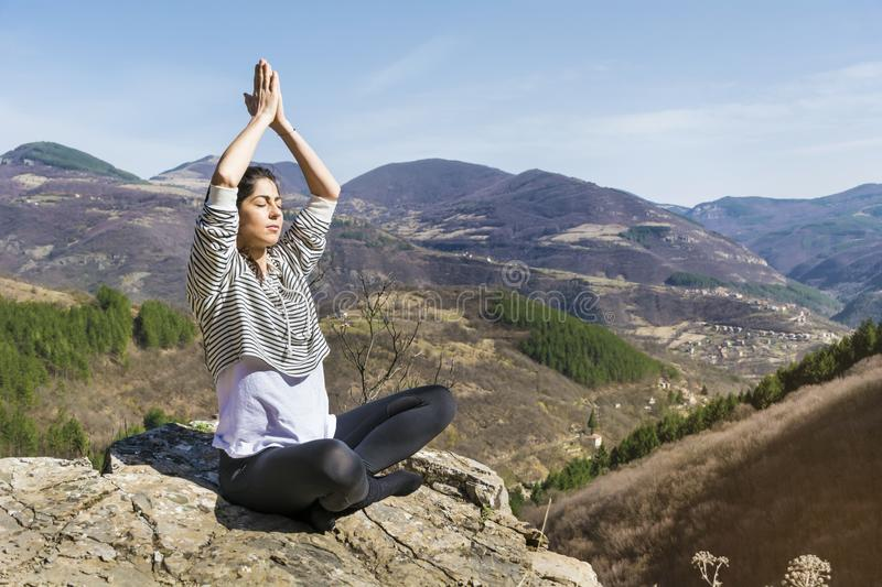 Young Woman Meditating in the Mountain. Young girl doing yoga fitness exercise outdoor on a beautiful mountains landscape royalty free stock images