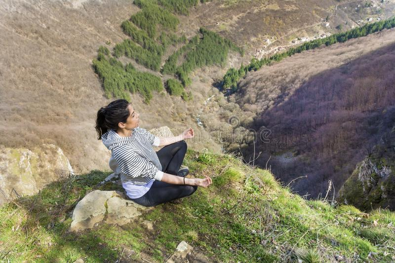 Young Woman Meditating in the Mountain. Young girl doing yoga fitness exercise outdoor on a beautiful mountains landscape royalty free stock photos
