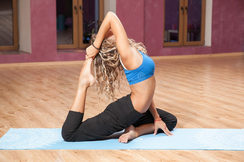 Young girl doing yoga on mat indoors stock photos
