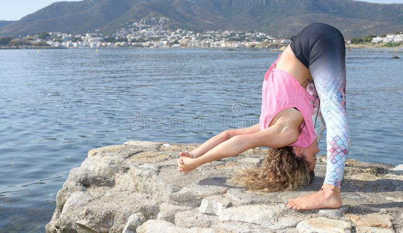 Young girl doing yoga on a small beach pier with a Mediterranean coastal town in the background. Staying fit. With copy space. stock photo