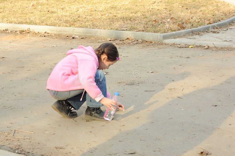 Young girl drawing on sidewalk stock images