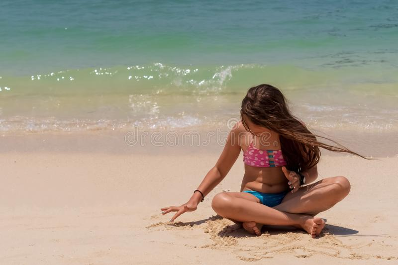 A young girl draws on the sand with a finger, the wind develops her hair royalty free stock photos
