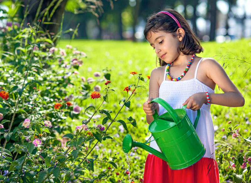 Young Girl in Dress Watering Plants. stock photos
