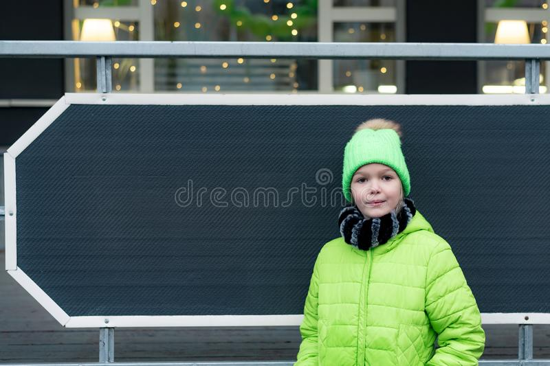 Young girl dressed in green jacket and hat stands in front of clean black board of decorated store, cafe, place for text royalty free stock photos