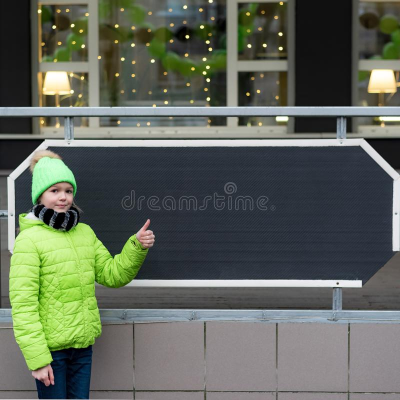 Young girl dressed in green jacket and hat stands in front of clean black board of decorated store, cafe, place for text stock photo