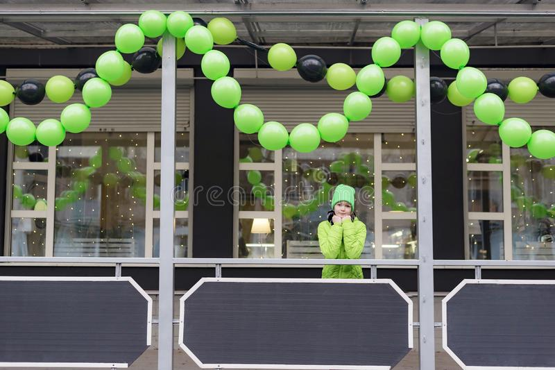 Young girl dressed in light green jacket and hat standing on the street at the glowing shop window royalty free stock photo