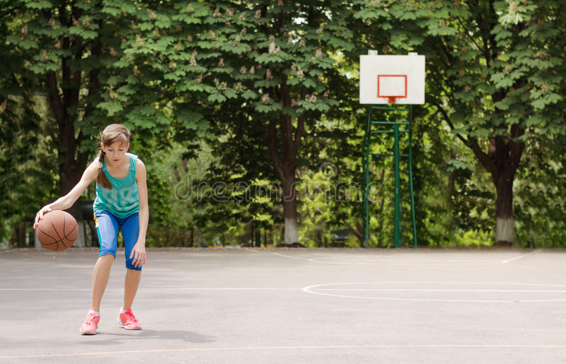 Young girl dribbling a basketball. Sporty young girl dribbling a basketball in an outdoor court royalty free stock images