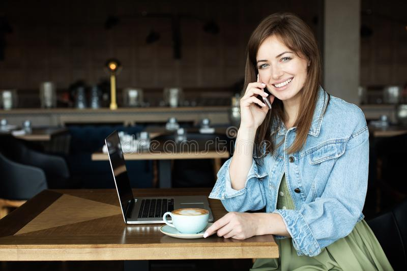 Young girl drinking coffee and talking on the phone royalty free stock images