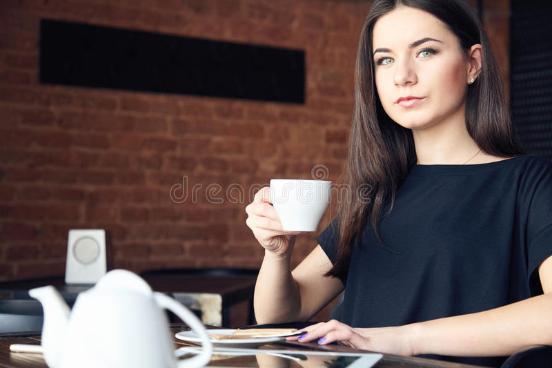 Young girl drinking tea in cafe and holding cup royalty free stock image