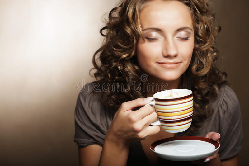 Young girl drinking tea or coffee. Beautiful young girl drinking tea or coffee stock images