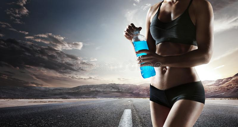 Young muscular build woman silhouette drinking water of bottle. Young girl drinking water of bottle after running, attractive athlete resting after workout stock image