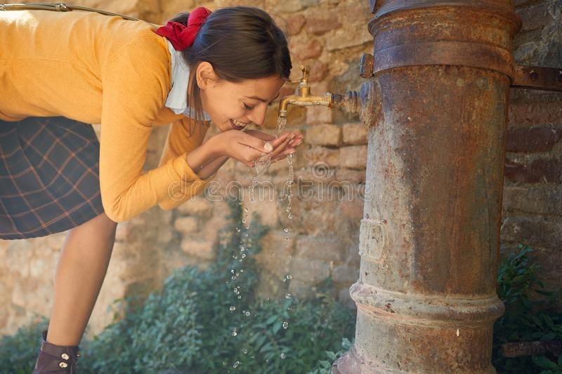 Young girl drinks from a drinking fountain stock photo