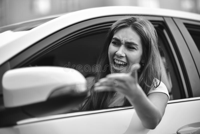 Young girl driving a car shocked about to have traffic accident, windshield view. stock photography