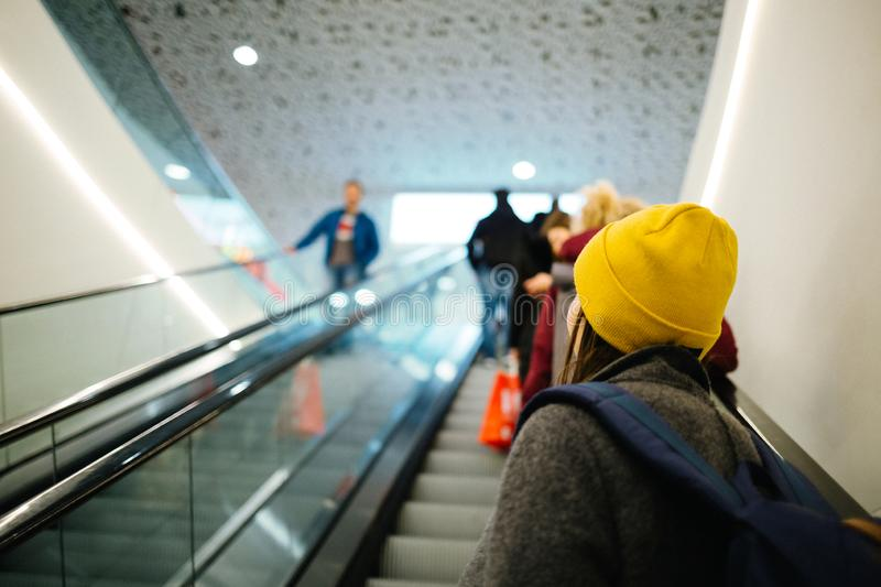 Young girl driving up at an escalator in a mall stock image
