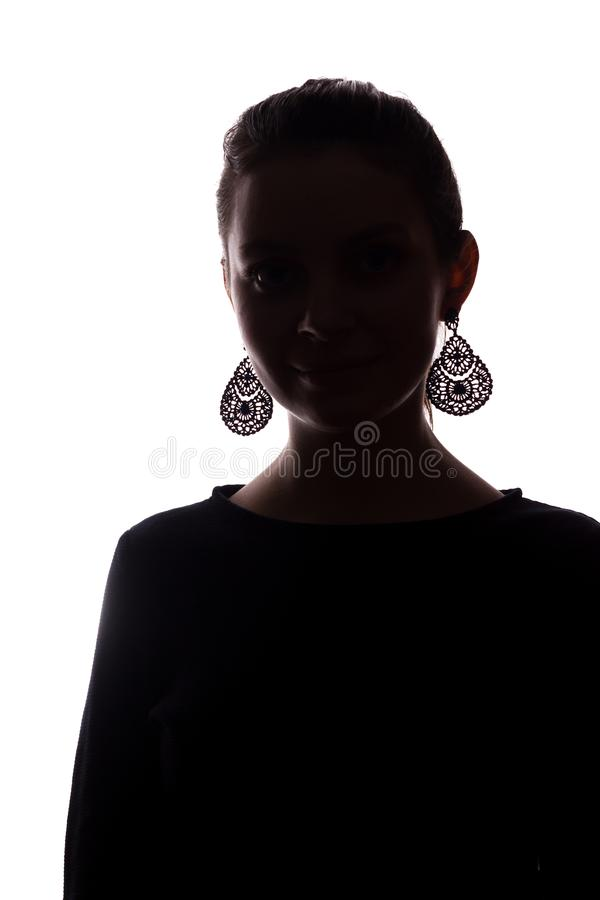 Young girl with earrings looks straight ahead, portrait isolate silhouette royalty free stock photos