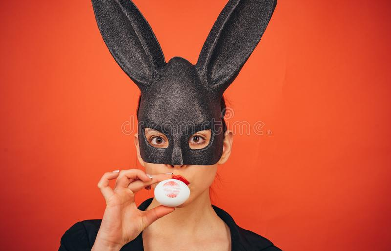 Young girl easter, woman in bunny ears. Red lip imprint on easter egg on red background. Print of red lips. Bunny mask royalty free stock photo