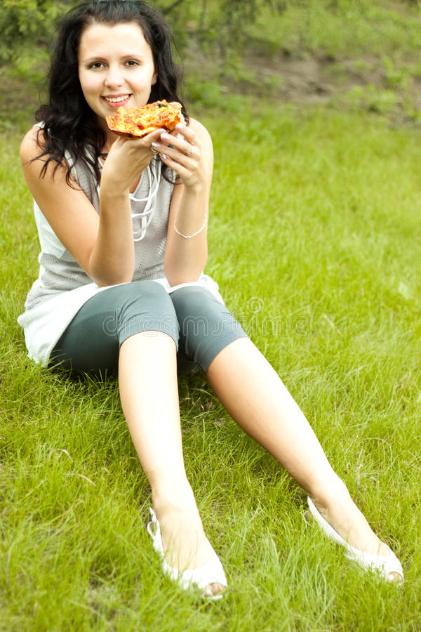 Young girl eat pizza. Slim brunette with long hair; beautiful happy young girl eat pizza stock photography
