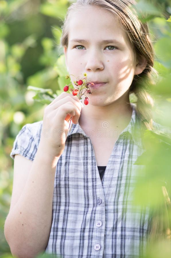 Young girl eating berries in nature stock photos