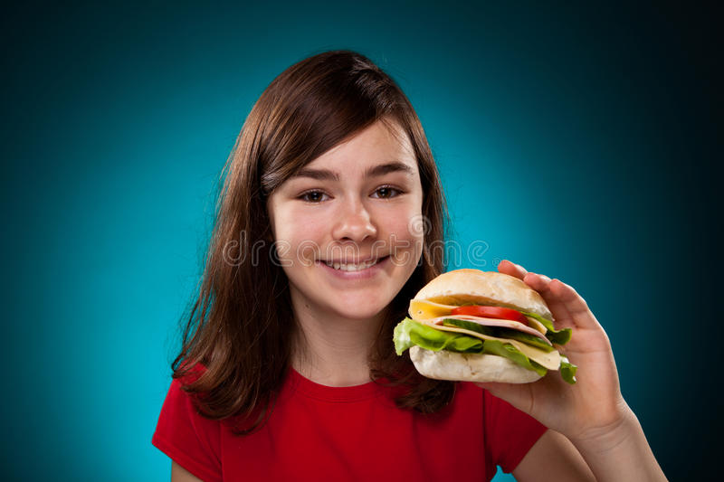 Young girl eating big sandwich royalty free stock image