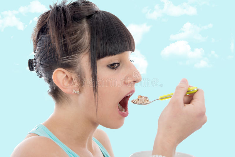 Young girl eating breakfast cereal. Young brunette girl eating breakfast cereal stock photo