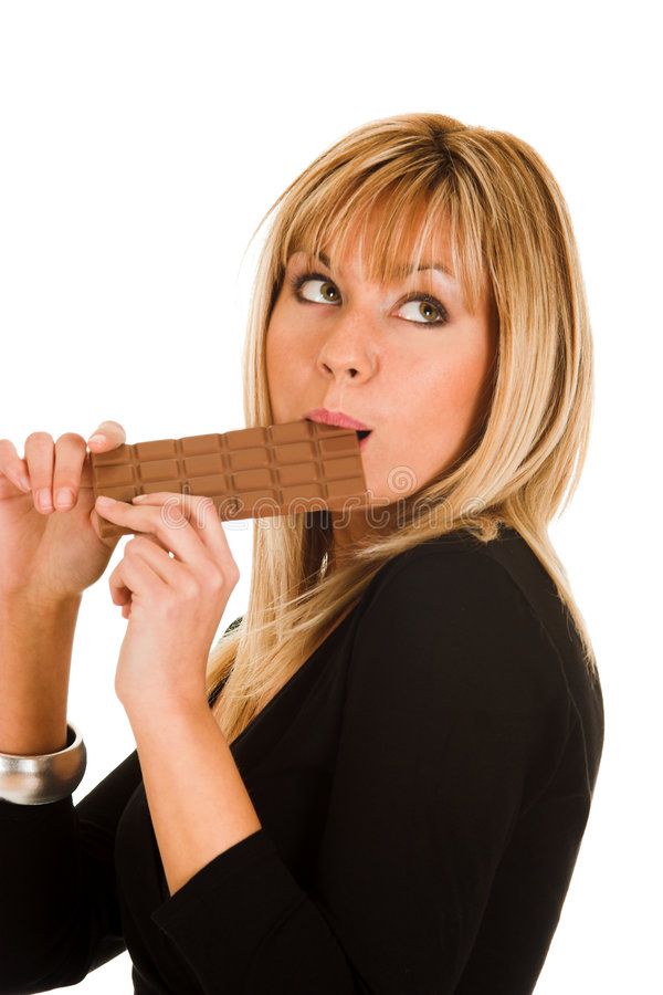 Young girl eating chocolate royalty free stock images