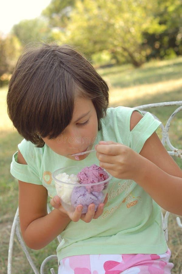 Young girl eating ice cream stock photography