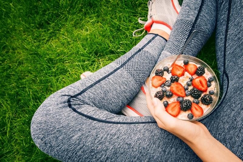 Young girl eating a oatmeal with berries after a workout . royalty free stock image